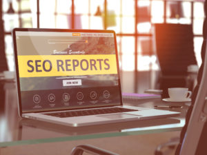 Computer with yellow SEO Reports website on it.
