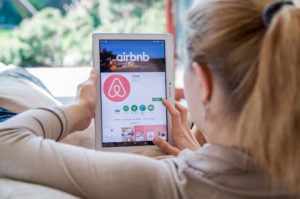 A woman looks at Airbnb's website on a tablet.