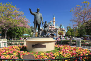A statue of Walt Disney holding hands with Mickey Mouse at Disney Land