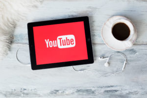 A cup of coffee and a pair of headphones sit next to an iPad displaying the YouTube logo.