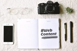 glasses, camera, pen, and open notebook with