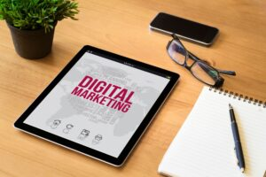 digital marketing print displayed on tablet that is on desk next to plant, glasses and open notebook